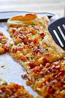 Honey-Caramelized Onion Tart - sweet onions are cooked with a honey/wine mixture, sprinkled over a sour cream layer and topped with fresh Thyme - all on an easy puff pastry pulled from the freezer. YUM.