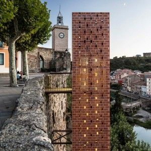 Perforated brick elevator by Carles Enrich connects medieval Spanish town to riverside