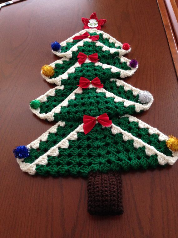 Christmas tree wall hanging made out of granny squares and decorated with bows and small ornaments. Star at top is crocheted.