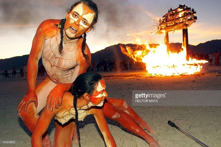 Thomas Wood and his companion, artists based in California, perform in front a wood structure set in fire at Black Rock City's Burning Man festival in Nevada 04 September 1999. Founded in 1986 by a group of fine artists, film makers and photographers, the annual event encourages a collaborative response from its audience and a collaboration between artists. (ELECTRONIC IMAGE) AFP PHOTO/Hector MATA
