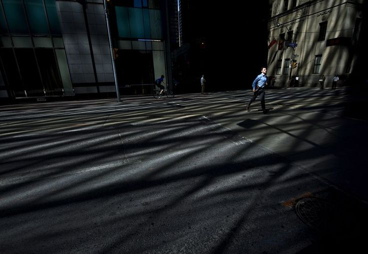 A businessman runs across Bay Street in Toronto's financial district as the morning light sweeps across the street. (Canadian Press)