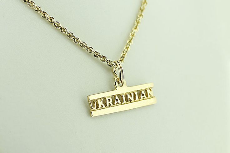 """Show off your Ukrainian pride with this bold 14kt gold pendant featuring the just one word: """"Ukrainian."""""""