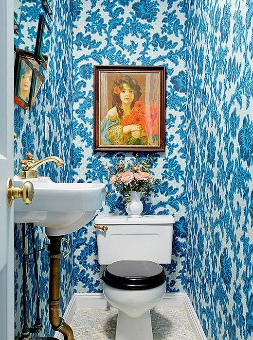 Brighten up a tiny half-bathroom with bold blue and white floral wallpaper and colorful artwork!