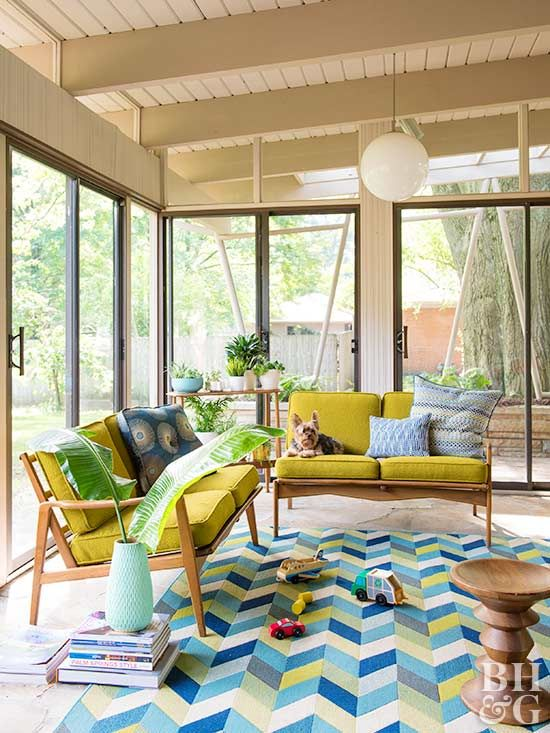 Covered porch ideas span from cottage style to contemporary. Add a modern vibe to a summer porch design with retro patio furniture and a geometric area rug. A basic midcentury pendant provides lighting for late-night entertaining.