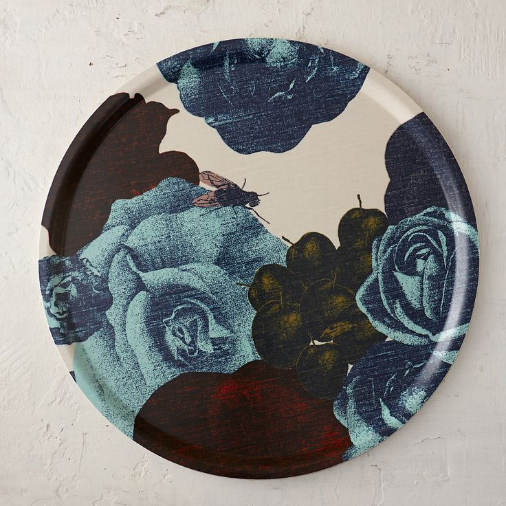 """Decked in a lush, floral pattern from Swedish graphic designer Lisa Bengtsson, this spacious serving platter pairs a fabric overlay with a lightweight base that makes it easy to carry from kitchen to table.- Fabric, plastic- Hand wash- Sweden0.5""""H, 18"""" diameter"""