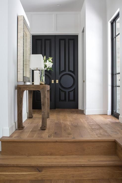 Dana Benson Construction - Exquisitely designed foyer boasts a black and white mirror mounted above a wood chinosiserie console table topped with a white table lamp and placed on rustic wood floors that lead to black circle paneled double front doors finished with gold knobs.