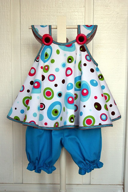 """Jelly Bean Sundress and Bloomers Patterns used to make this outfit were """"Sheri's Cherries"""" by Kari Mecca for the top and """"Hallie"""" for the knee length bloomers.The jelly bean pique print and turquoise pique solid are both by Fabric Finders. The trim is pre-cut bias in brown check and turquoise baby ric-rac sewn on top of the folded bias. Kits to make this outfit are available now in the webstore! Go here to find it www.sewblessedfabric.com/index.php?option=com_virtuemart&..."""