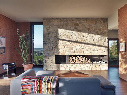 Living room with a great fireplace in a stone wall   love the stone and brick texture and colors !
