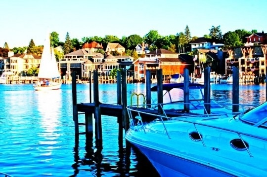 Lake Charlevoix, Michigan.  Gorgeous lake village that feeds into Lake Michigan.  Enjoy a nice calm boat ride thru the village and then enter a canal that puts you into Lake Michigan.  Like jumping into the wild ocean!  This is a wonderful summer vacation spot.  Very warm...yet not scorching!  Wonderful place for sailing or jet skiing.