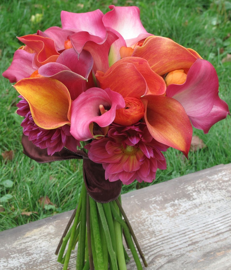 Bouquet of pink and orange callas with ranunculus and dahlias.