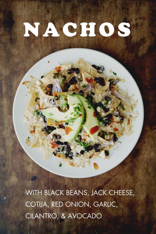 Nachos with Black Beans, Jack Cheese, Cotija, Red Onion, Garlic, Cilantro, + Avocado