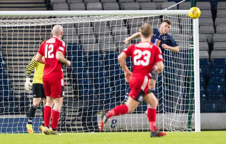 Queen's Park's Adam Cummins heads clear during the Scottish Cup round 4 replay between Queen's Park and Ayr United.
