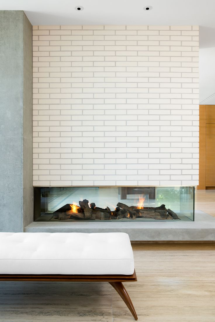 White brick fireplace.  By: Zacharko Yustin Architects Incorporated Photo: Ema Peter Photography
