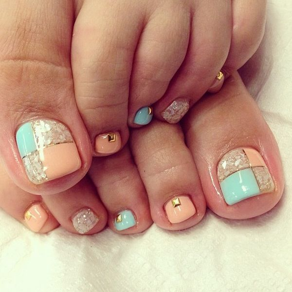 A very interesting and beautifully created toenail art design. An almost gingham like design that uses light blue and melon shades. The squares are lined with a thin gold coating and additional frosted white polish is added along with a square shaped gold bead placed on top.