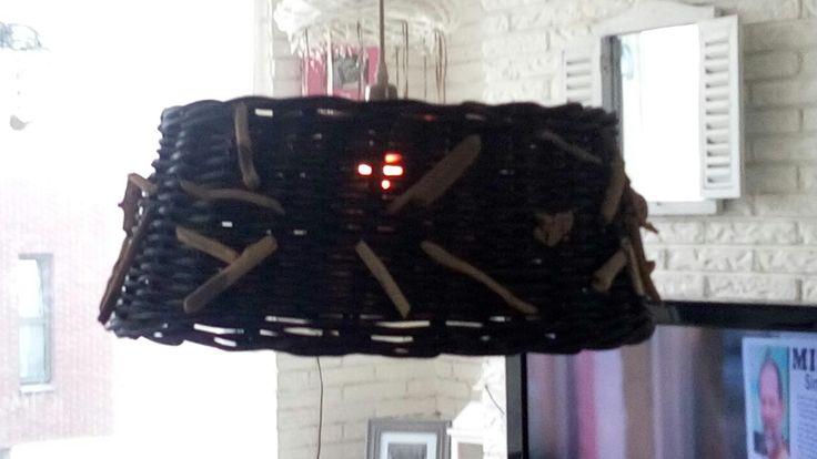 Van een oude rotan kerstboom mantel naar een te gekke lampenkap.  Geschilderd in het zwart en daarna bewerkt met stukjes drijfhout. (Gaatjes erin geboord en daarna vastgezet met dun ijzerdraad)
