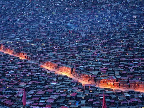 Larung Gar, China Photograph by Lei He, National Geographic Your Shot  Streetlamps light a path through a dense population of small homes with red roofs in Larung Gar, in the Garzé Tibetan Autonomous Prefecture, China. Some 10,000 nuns and monks live here, settled around one of the largest Buddhist institutes in the world.