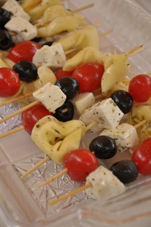 Skewers with tortellini, tomato, mozzarella and black olive, sprinkled with olive oil and oregano.
