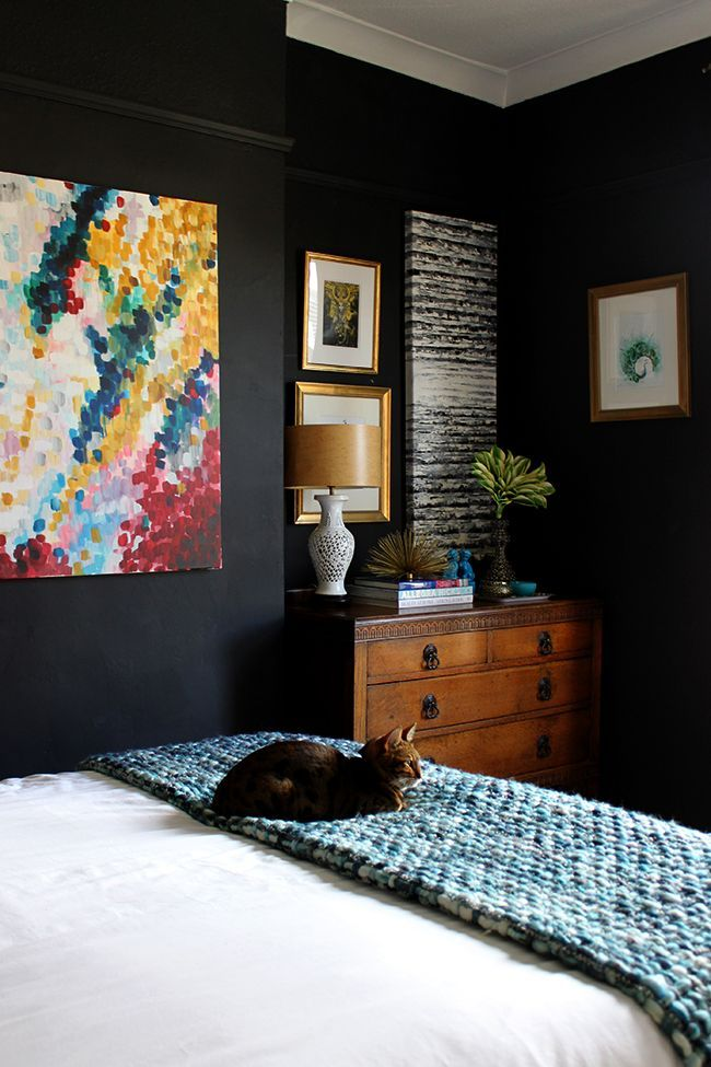 Bengal cat on bed - black bedroom with colourful art and vintage chest of drawers