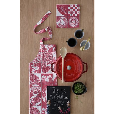 The red apron from Bjørn Wiinblad's range of textiles is made of printed cotton and decorated with plenty of jovial, well-known motifs from the artist's universe. #bjørnwiinblad