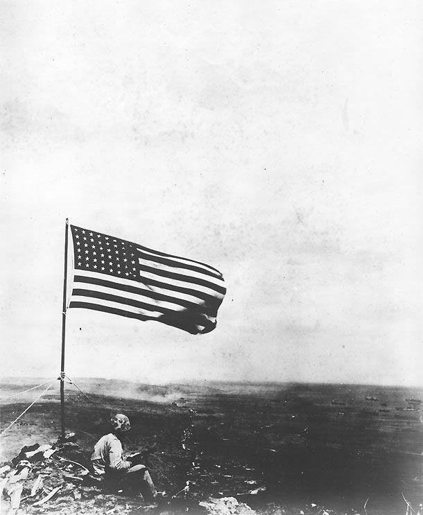 An American Marine sat beneath the American flag atop Mount Suribachi, Iwo Jima, Japan, 23 Feb 1945