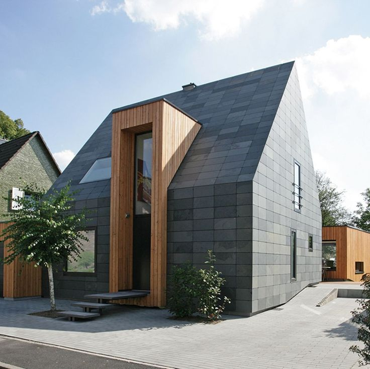 Contemporary black-clad #house with monolithic door/window projection #YankoDesign #Architecture #Design