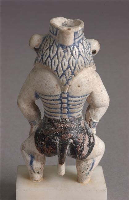 Faience kohl pot in the form of the god Bes, Dynasty XVIII, Egypt.  Note the tail.
