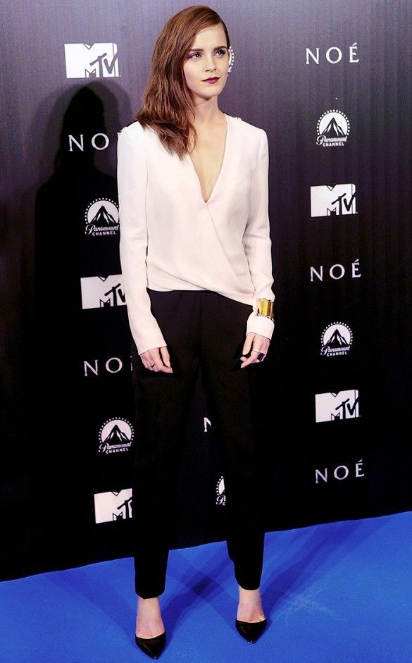 Emma Watson wears a white wrap top, black trousers, black pumps, and statement jewelry