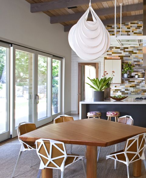 The kitchen table, designed by de Lisle from four-inch thick Douglas fir, is accented by bright white geometric chairs and a modern teardrop-shaped pendant light. © Art Gray Photography