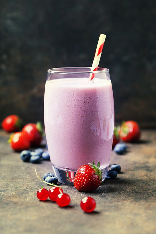 Strawberry smoothie and fresh berry on rustic background
