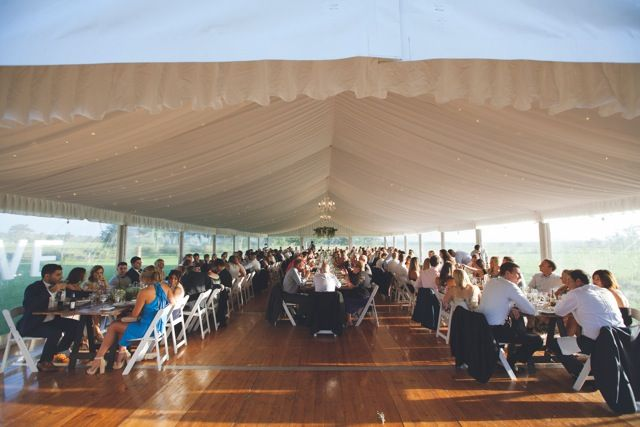 silk lining, chandeliers, 10m marquee weddings, integrated timber flooring, vintage timber tables, white padded folding chairs, clear walls, south coast weddings, south coast party hire