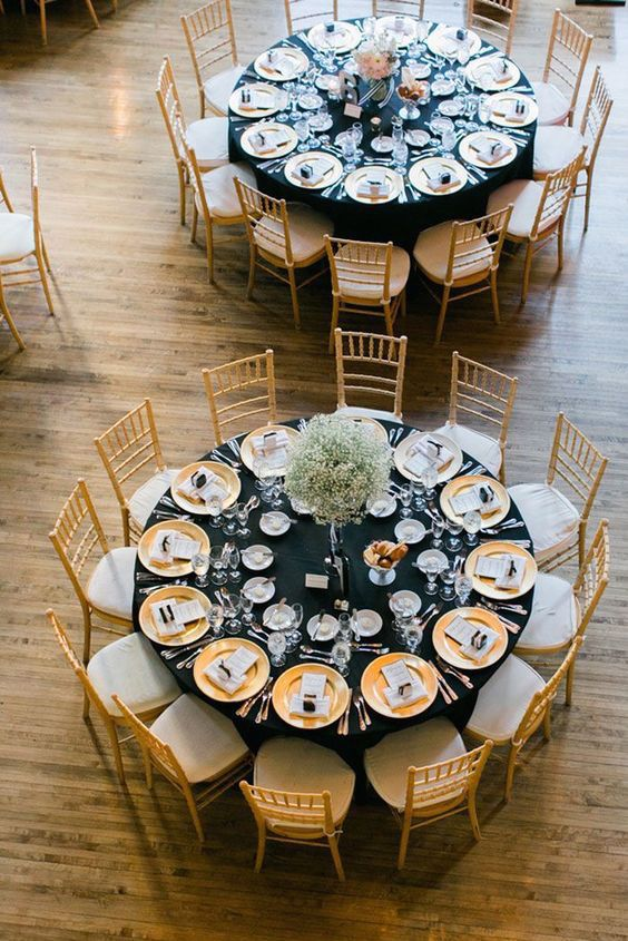 Manteles en negro con sillas y vajilla en dorado para la recepción de bodas en negro y dorado.