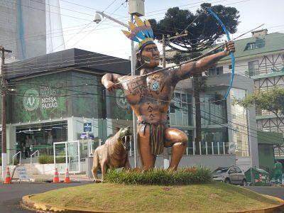 Índio Condá em frente à Arena Condá em Chapecó. Atrás, pode ser vista a loja oficial do time do Chapecoense.