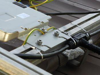 Montage der Wechselrichter auf den Montageschienen. Erdungskabel nicht vergessen. AC Trunc Cable muss in der richtigen Richtung gelegt werden. Dran drenken, die Panels müssen eingesteckt werden und die Kabel sind meistens nicht so lang!