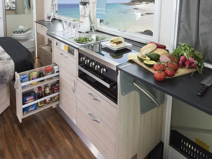 The kitchen in the C7424SL Birdsville motorhome is well equipped and features a clever benchtop extension which folds out in front of the door for more bench space. The pull out pantry is also a handy way to store the favourites.
