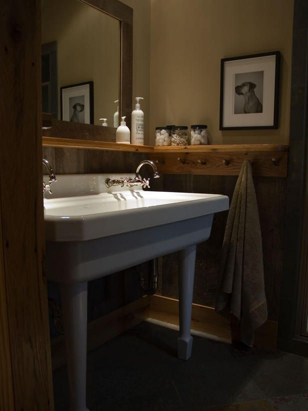 Several pegs line a wooden rail in Dream Home 2006's bunk bathroom, providing plenty of room to hang towels, toiletries and other bathroom items. A wooden shelf sitting atop the peg rail gives room for lotions and jars filled with toiletries.