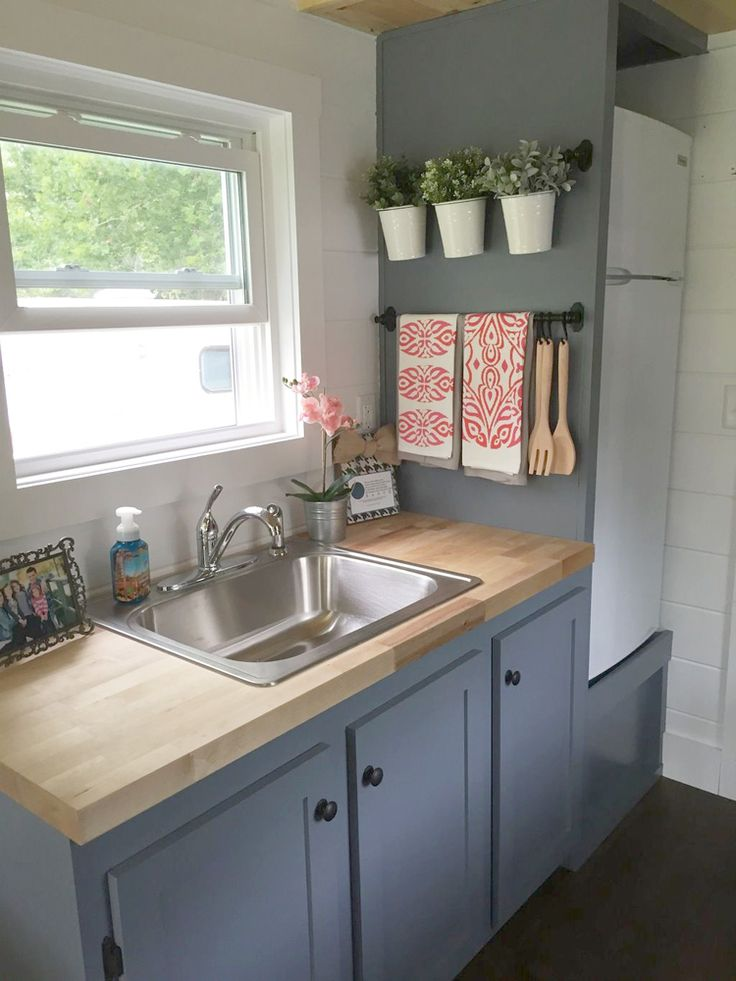 In the galley kitchen are blue-grey cabinets, butcher block counters, a four-burner gas stove, and an apartment size refrigerator.