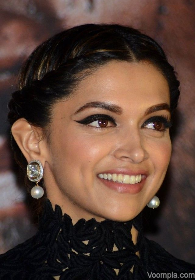Words are not enough to describe how beautiful Deepika Padukone looks in this lovely closeup photograph. Her hair has been styled by Daniel Bauer into a classic updo with braids, and her heavy smokey eyes add a dramatic twist to her look. The actress is wearing earrings by Anmol Jewellers. via Voompla.com