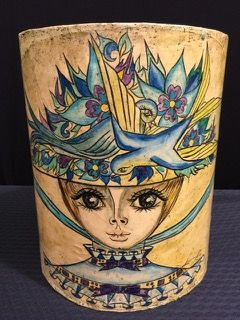 HANDCRAFTED PAPIER MACHE WASTE BASKET BY MEXICAN FOLK ARTIST ABELAROO RUIZ. EGG CREAM BASE WITH TURQUOISE INSIDE AND PURPLE AND YELLOW TOUCHES. DEPICTS A VICTORIAN WOMAN WITH LARGE FLORAL AND BIRD HAT. MEASURES 11 INCHES HIGH BY 9 INCHES IN DIAMETER. SLIGHTLY MARRED AROUND THE RIM