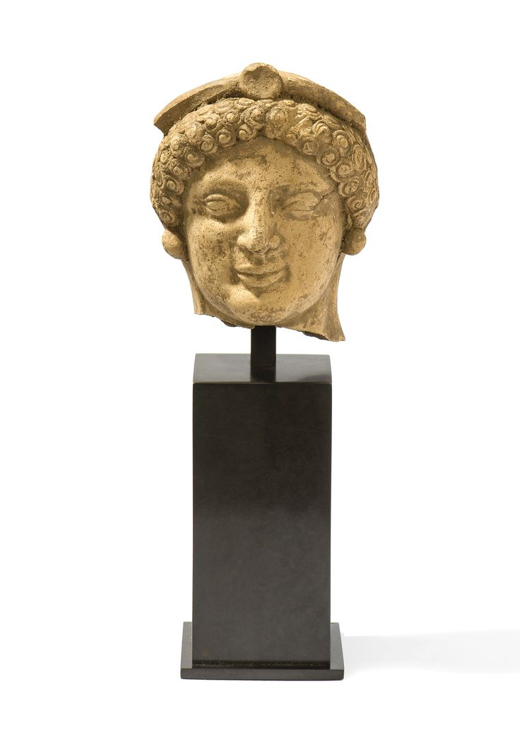 Greek archaic kore head, Hipponion, Vibo Valentia, 5th century B.C. Greek archaic terracotta kore head, Hipponion, Vibo Valentia. Almond shaped eyes, greek smile, curly hair surmounted by diadem,  round earrings, 10,5 cm high. Private collection, ex Virzi collection