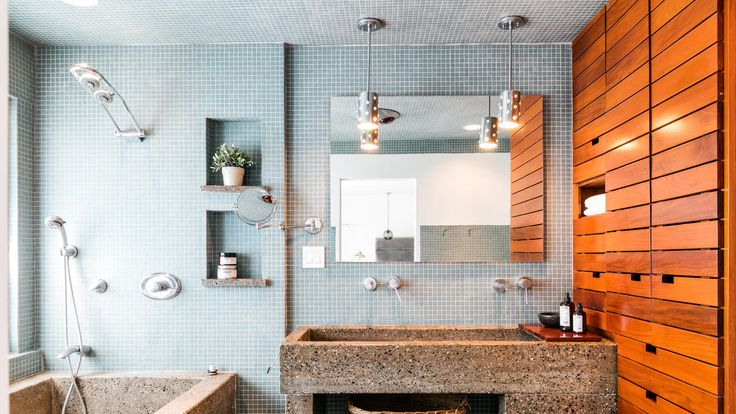master bathroom, where wood shelving provides a warm counterpoint to blue tiles and a concrete sink and tub.