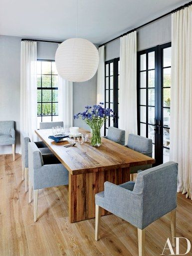 A Noguchi-designed paper light fixture hangs above the handsome wood dining table in this Hamptons home by Sawyer|Berson | archdigest.com