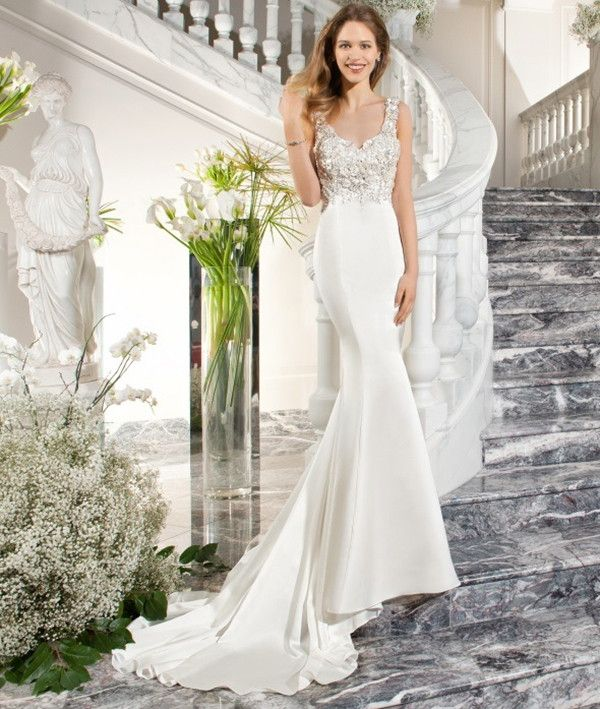 This elegant, luxe satin, form-fitting wedding gown features a unique design of beaded embroidery and jewel encrusted rosettes on the bodice and throughout the dramatic illusion back with button closure.