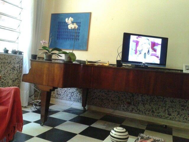O piano de cauda inteira na sala de jantar, sem teclado, que serve de apoio pra TV.