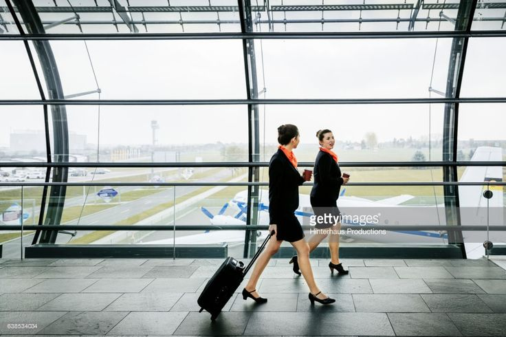 Two female flight attendants are on their way to their flight. Both walking through airport hallway.