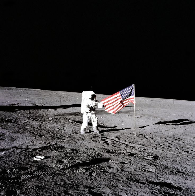 "Apollo 12 astronaut Charles ""Pete"" Conrad stands beside the United States flag after is was unfurled on the lunar surface during the first extravehicular activity on November 19 1969. Several footprints made by the crew can be seen in the photograph. [3000 x 3026] http://ift.tt/2izUTqh"