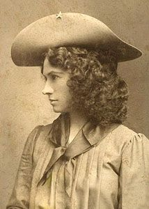 Annie Oakley (August 13, 1860 – November 3, 1926) was an American sharpshooter and exhibition shooter. Oakley's amazing talent and timely rise to fame led to a starring role in Buffalo Bill's Wild West show, which propelled her to become the first American female superstar.  Oakley's most famous trick is being able to repeatedly split a playing card, edge-on, and put several more holes in it before it could touch the ground, while using a .22 caliber rifle, at 90 feet. [Wikipedia]