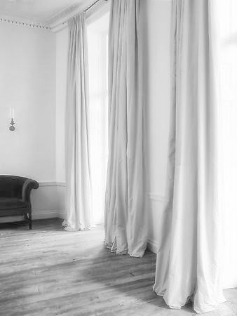 Black & White www.annagillar.se grey wooden flooring white walls long grey drapes armchair minimalist