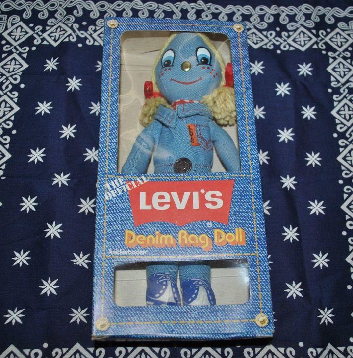"""推定年代1970年代前半のリーバイス デニム ラグドールを紹介します。オリジナルの箱付きです。箱の状態も良好です。人形のコンディションも良好で、未使用、デッドストック相当と判定しています。 箱の後ろ側の写真です。""""The Official""""、その下にリーバイスのバットウィングのロゴ、続いて""""Levi's Denim Rag Doll""""の表示があります。スタイル番号は3608です。 製造メーカー・ブラン..."""