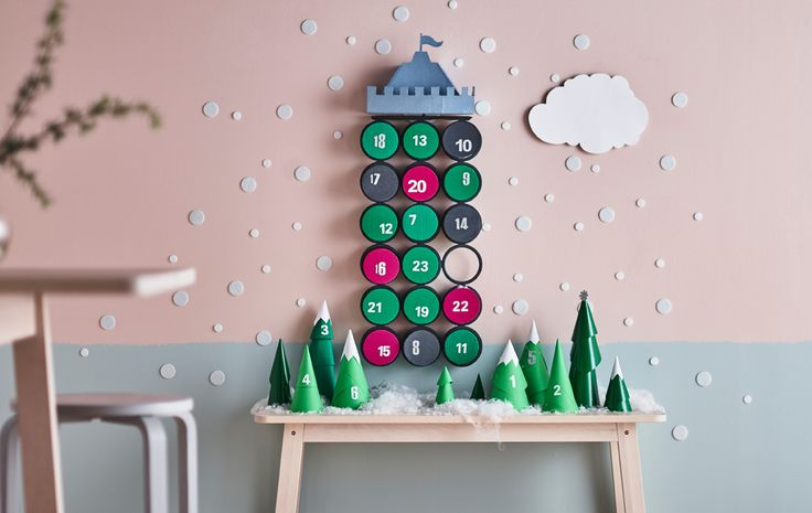 An advent calendar display with paper trees on a table and a castle hanging on a wall