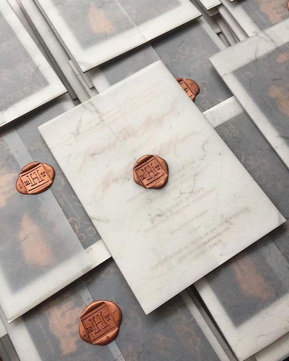 Maravillosas invitaciones con papel de manteca marmolado y un sello color cobre.